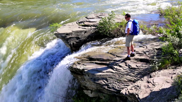 Male hiker overlooks waterfalls video