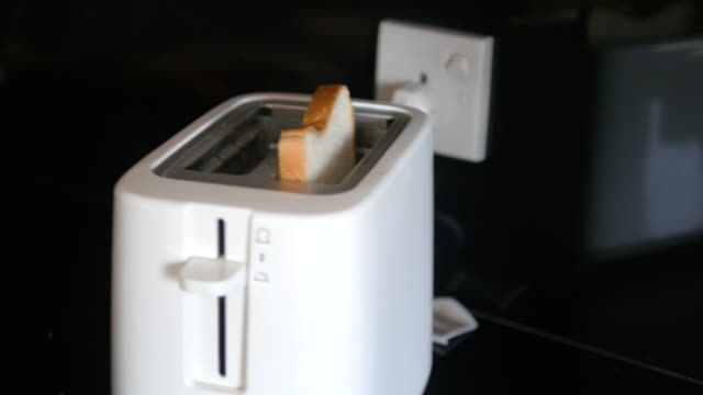 Male indian hands put in toaster two slices of bread, and then toasted. Close up video