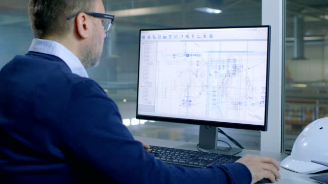 Male Industrial Engineer Works on His Computer with Technological Blueprints. Inside of the Factory is Seen From Her Office Window. video