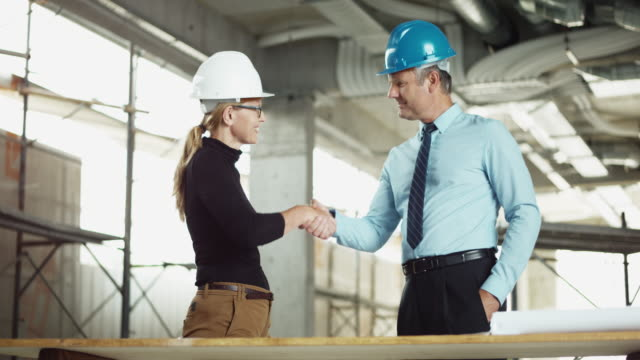 DS Male investor shaking hands with female architect at the construction site video