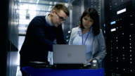 Male IT Specialist Shows Information on a Laptop to Female Server Technician. They're Standing in Data Center. video