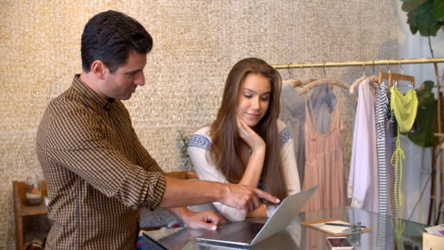 Male manager and female trainee using laptop in clothes shop video