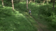 AERIAL Male marathon competitor running across forest clearing video