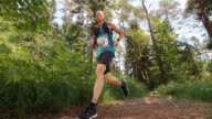 SLO MO CS Male marathon competitor running on forest trail video