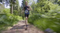TS Male marathon runner running on forest path in competition video