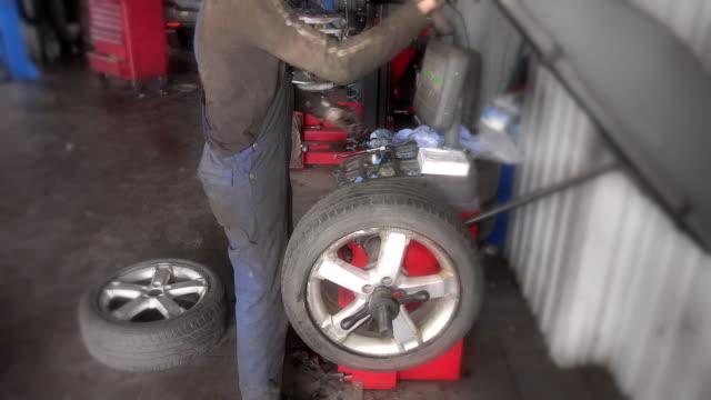 male mechanic balancing car wheel on balancer in repair service video