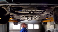 Male mechanic examining lifted automobile parts at auto repair shop video