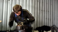 male mechanic grind rusty metal with rasp tool in garage. video