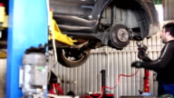male mechanic with cigarette repairing car brake system video