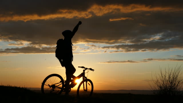 4К Male mountain biker standing on top, hand raised video