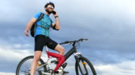 4К Male mountain biker talking on phone on top video