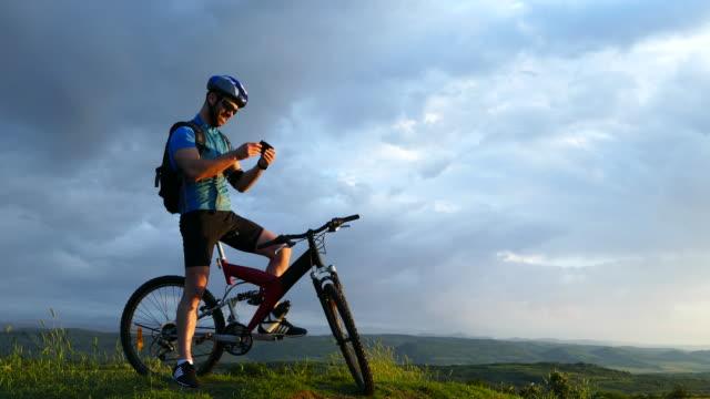 4К Male mountain biker using smart phone on top video