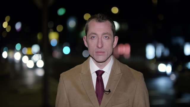 Male news reporter reporting live to the studio from the city at night video