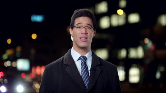 Male news reporter reporting live to the studio from the city center at night video