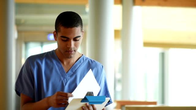 male nurse checking notes in a hospital corridor video