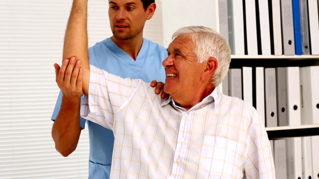 Male nurse showing elderly patient how to exercise his arm video