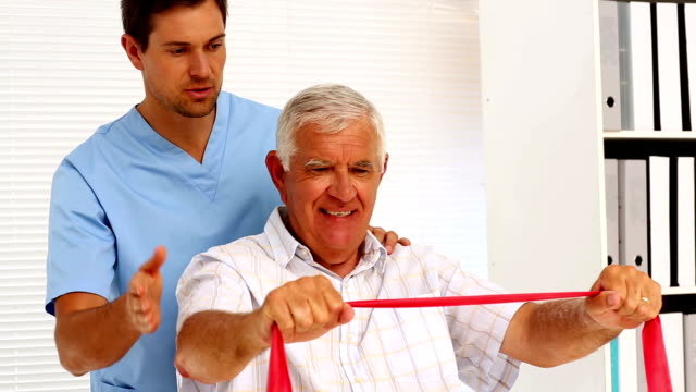Male nurse showing elderly patient how to use resistance band video