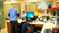 Male nurse taking paperwork from patient video
