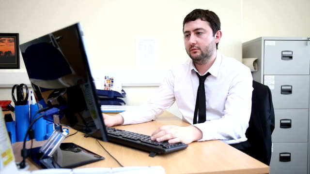 Male office worker at computer video