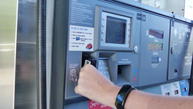 Male paying gas station plastci card video