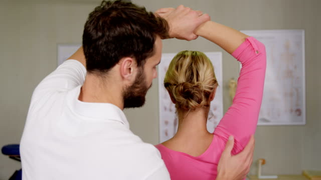 Male physiotherapist giving arm massage to female patient video