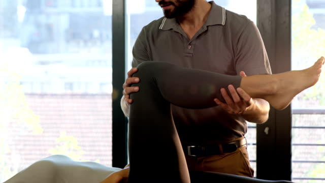 Male physiotherapist giving leg massage to female patient video