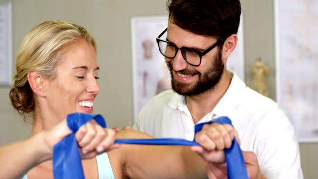 Male physiotherapist giving shoulder massage to female patient video