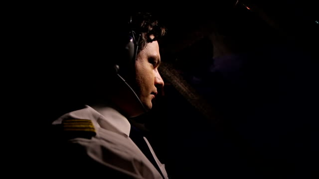 Male pilot in headset flying airliner and checking flight panel, aviation video