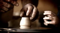 Male potter teaches his little pupil to make a pot from scratch video