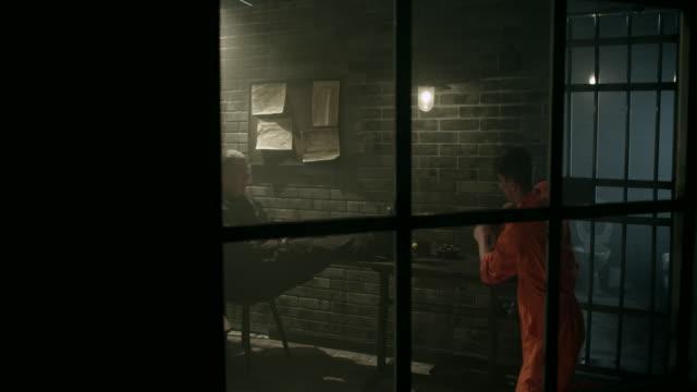 Male prisoner cleaning table in jail thru window video