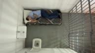4K AERIAL: Male Prisoner in Jail Cell can'r get to sleep video
