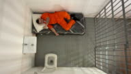 4K AERIAL: Male Prisoner in Jail Cell tring to sleep video