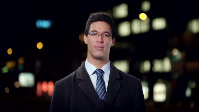 Male reporter reporting live from the city at night video