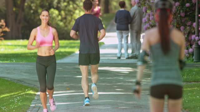 SLO MO Male runner giving a high five to his partner as she runs by him video
