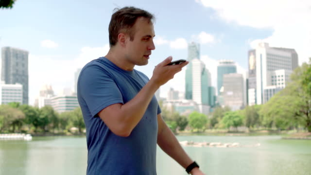 Male runner jogging in park. Fit male sport fitness training. Talking on his smartphone video