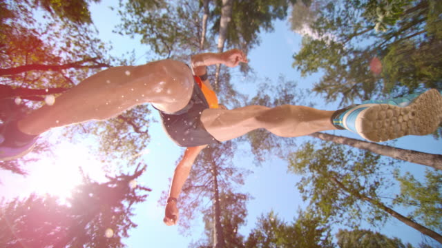 SLO MO Male runner makes a jump in sunlit forest video