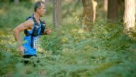 SLO MO DS Male runner running through forest in competition video