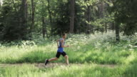 SLO MO Male runner running on a forest trail in sunshine video