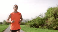 SLO MO TS Male runner running through park video