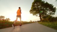 SLO MO TS Male runner running in countryside at sunset video