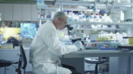 Male scientist is working on a microscope in a laboratory. video