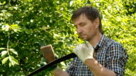 A male sharpening scythe tool with stone in in hot summer day video