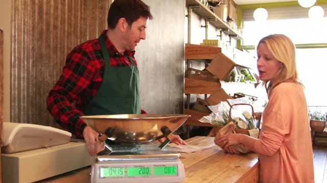Male shop assistant serving customer video