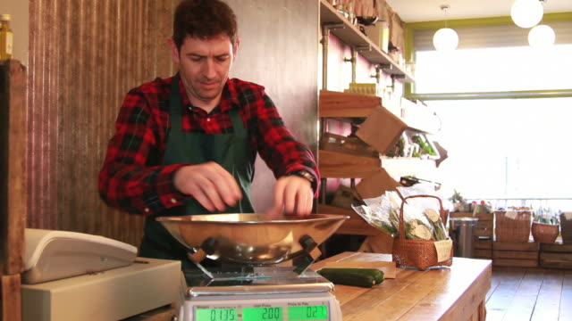 Male shop assistant weighting vegetables video