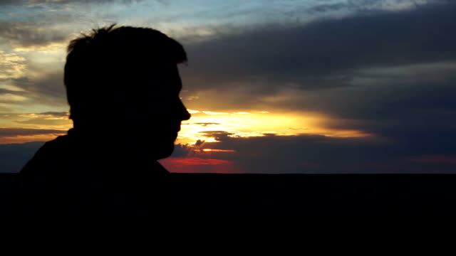 Male silhouette at sunset, man looking at sky, thinking about life, memories video