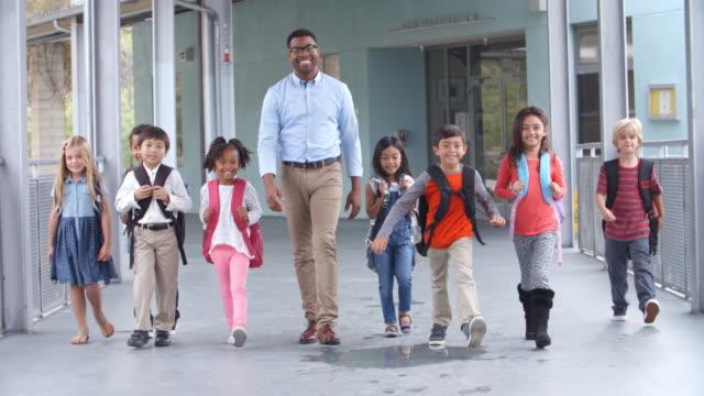 Male teacher walking in corridor with elementary school kids video