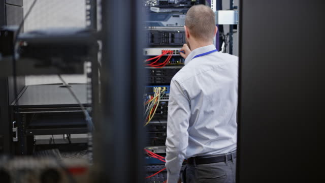 DS Male technician connecting cables in the server room video