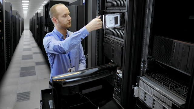 LD Male technician in the server room inserting hard discs video