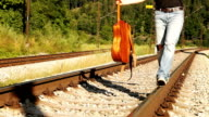 A male teenager walks balancing along the railway with the guitar video