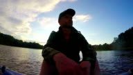 Male tourist having rest after paddling boat. Action cam, slowmo video
